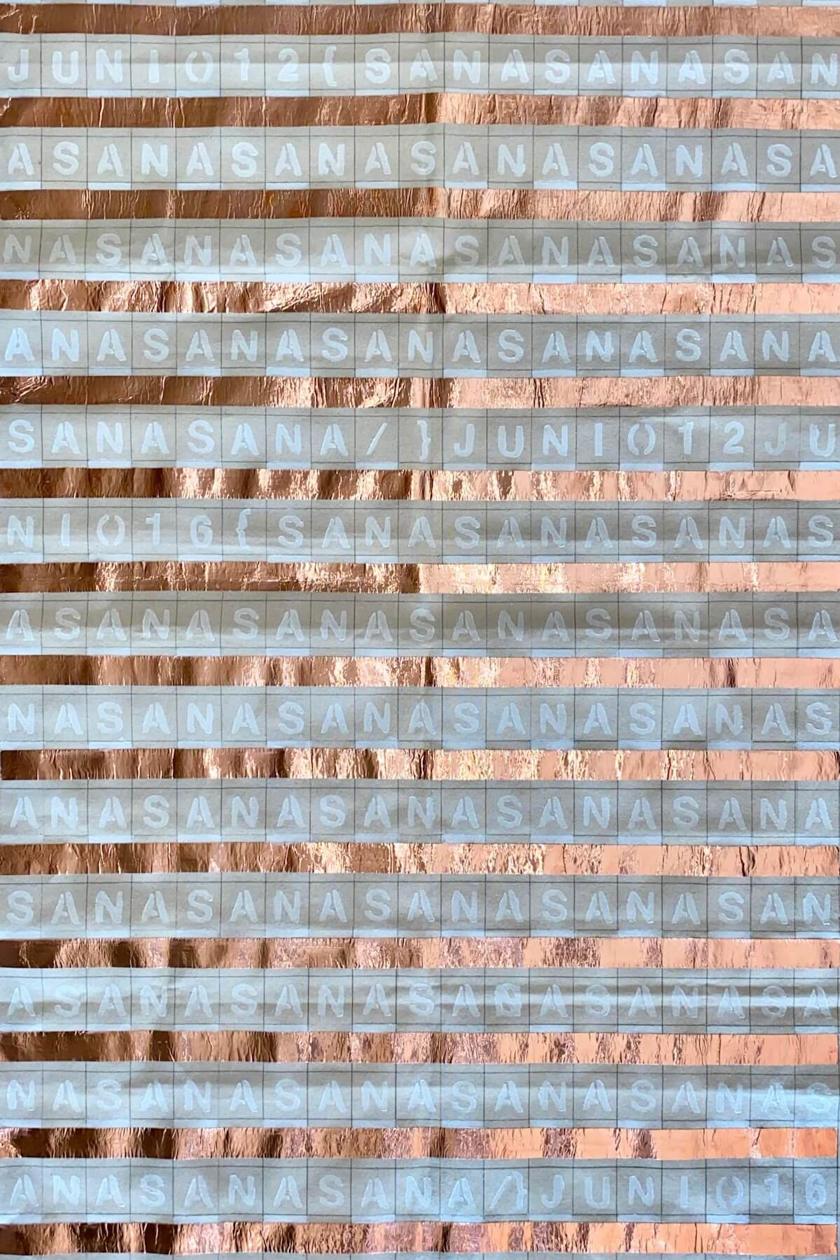 Brown paper divided into a grid. Every other row is striped with shiny copper foil. Between those stripes, each square of the grid contains a letter printed in white forming a continuous stream of letters reading 'ASANASANASANASANA'.