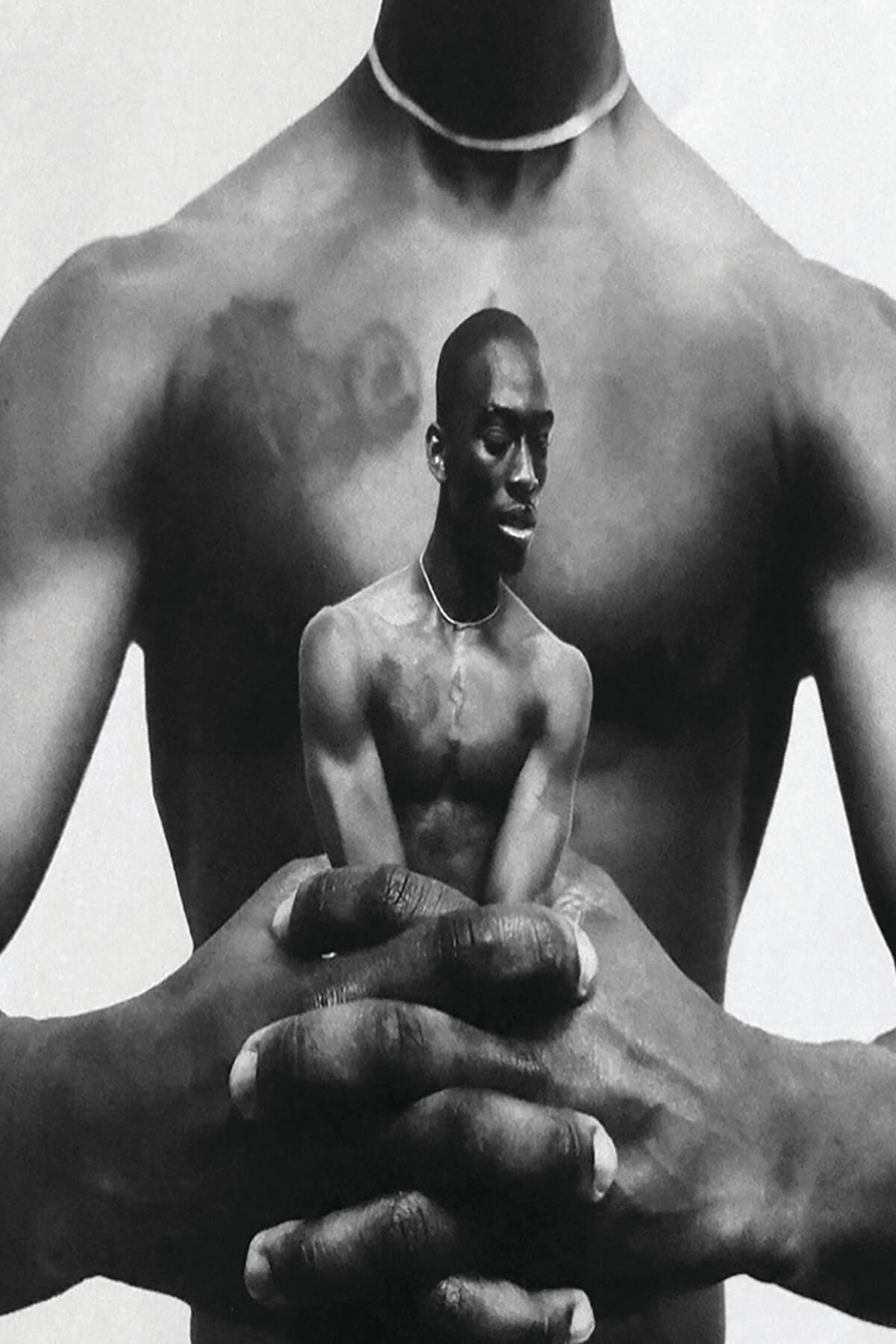 A black and white photo collage. The bare torso of a black man extends his arms forward and clenches his hands together. Caught within those hands is a smaller image of the shirtless black man, his arms constrained by the large hands within which he's held.