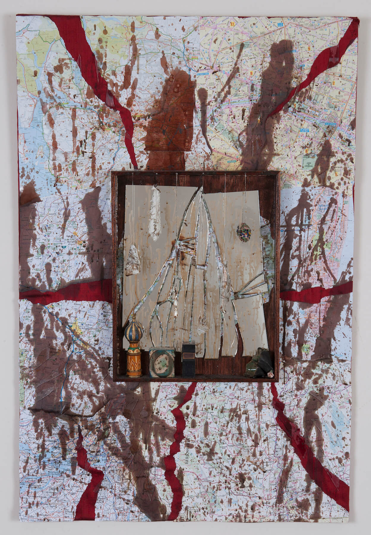 A mixed media artwork that features an abstract background in red, white and brown and a centered altarpiece. The altarpiece background is made of shattered glass and small objects are placed on the bottom ledge of the altar.