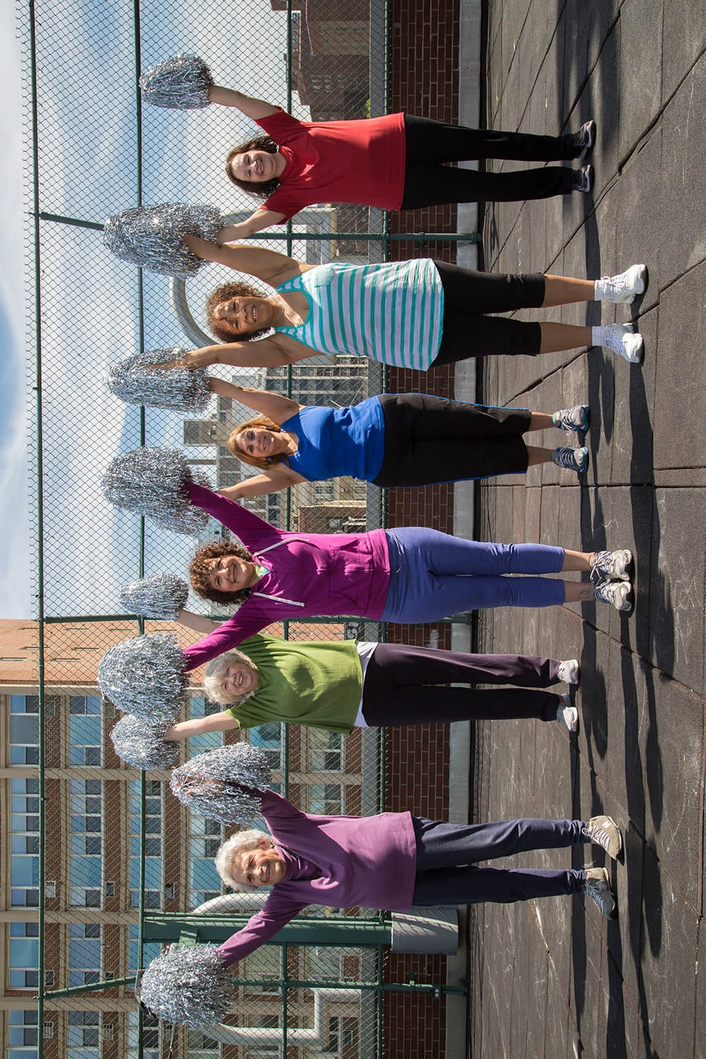 A photograph, exterior on a sunny day - 6 smiling elder women in workout clothes stand in formation on the rooft of a building in a big city, holding silver cheerleader pom-poms over their head, about to cheer.