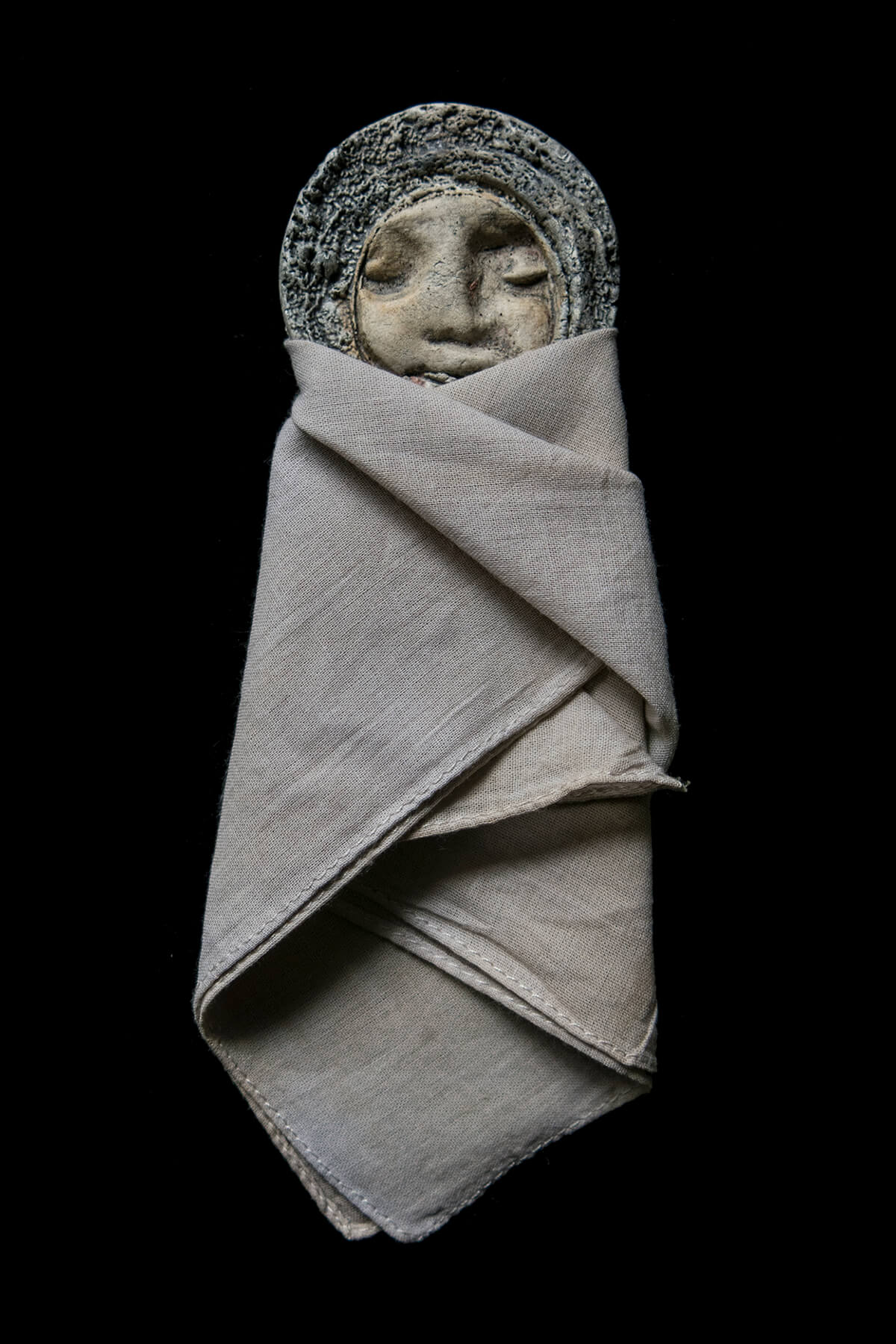 A photograph of a figurine with a round medallion-like head with eyes closed. The whole rest of the body of the figurine is swaddled in rough cloth, wrapped carefully like a small child.