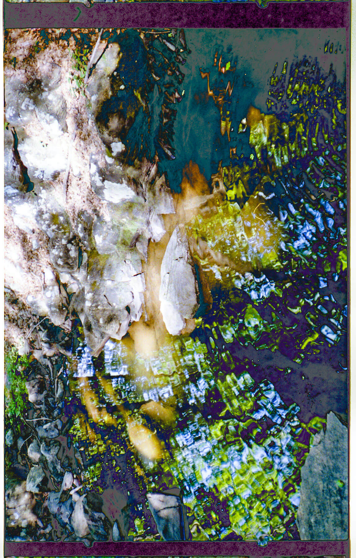 A photograph with layered exposures of rocks and water. The colors are vivid blues, greens, yellows, and white on a dark background.
