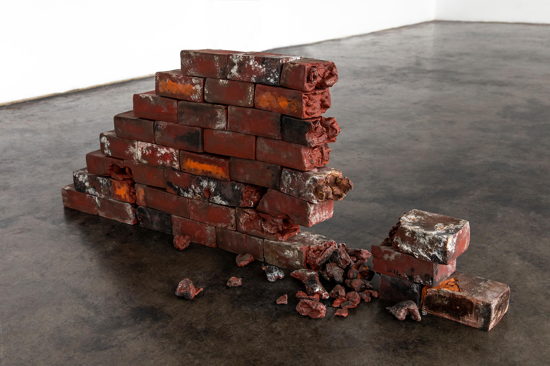 A photograph, interior to an art gallery. On the floor is a stack of rough bricks, mostly dark red but with some white, orange, and black paint. They are arranfed into a small triangular 'wall,' one brick thick, with a portion of the wall missing or collapsed, and on the smooth floor fragments of brick are scattered.