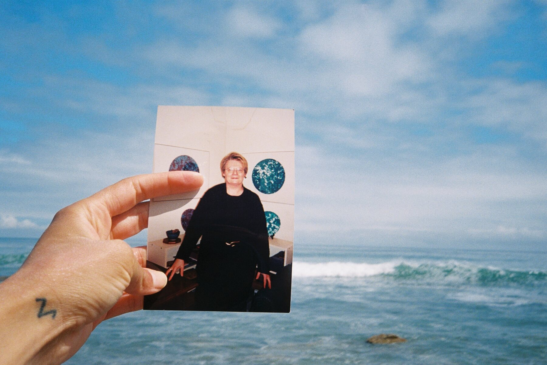 A photograph of a white person's hand holding a photograph of an older white woman. In the background is a large body of water.
